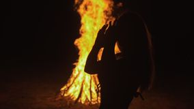 Silhouette of mystic woman in black background of fire fly flame, spark, of contour outline. Outdoor slow motion