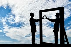 Concept of narcissism and selfishness. Silhouette of a narcissist man and a hand gesture of a heart in reflection in a mirror. The concept of narcissism and Royalty Free Stock Images