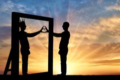 Silhouette of a narcissist man and hand gesture of a heart in reflection in the mirror and crown on his head. The concept of narcissism and selfishness stock photo