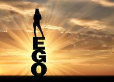 Silhouette of a narcissistic and selfish woman with a crown on her head standing on the word ego. The concept of narcissism and selfishness Stock Photography