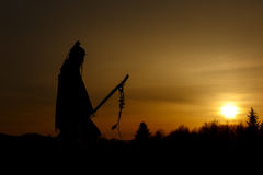 Silhouette of native american shaman with pikestaff on backgroun. D of sunset beutiful in mountains Royalty Free Stock Photos