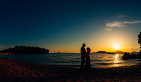 Silhouette of a newlywed couple at the sea at sunset. Wedding in Royalty Free Stock Photography