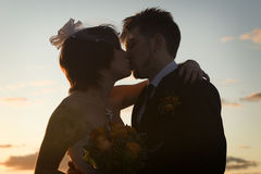 Silhouette of newlyweds kissing. Silhouette of young newlyweds kissing at sunset Royalty Free Stock Photo