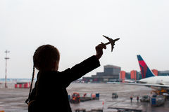 Silhouette noire d'un petit jouet de modèle d'avion sur l'aéroport dans des mains d'enfants images stock