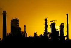 Silhouette noire de station de raffinerie de pétrole brut pendant le coucher du soleil Image stock