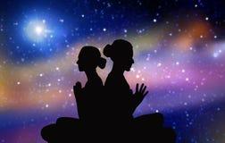 Silhouette noire des couples méditant au-dessus de l'espace Photographie stock