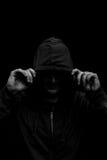 Silhouette noire et blanche d'un homme à capuchon, d'isolement sur le fond noir Photos libres de droits
