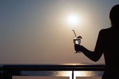 Silhouette of nude girl with cocktail in hands on sunset background. Silhouette of nude girl with cocktail in hands on sunset Royalty Free Stock Photography