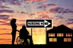 Silhouette of a nurse caring for an elderly man in a wheelchair Stock Photo