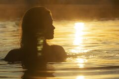Free Silhouette Of A Beautiful Girl With Wet Hair In Water, Head Of A Woman Bathing In A Hot Spring At Sunrise, Summer Relaxation And Royalty Free Stock Photo - 170421905