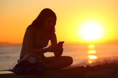 Free Silhouette Of A Girl Using A Smart Phone At Sunset Royalty Free Stock Image - 138452526
