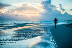 Free Silhouette Of A Man Running At Sunrise On A Beach Stock Photography - 125690382