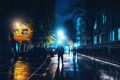 Free Silhouette Of Alone Stranger In Hood At Night City Street In Rain. Creepy Killer Or Stalker, Criminal Stands In Shadow Royalty Free Stock Image - 200731996