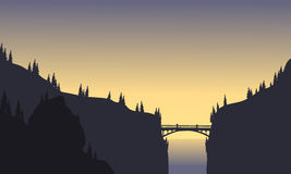 Silhouette Of Bridge Connecting Two Cliffs Royalty Free Stock Photography