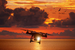 Free Silhouette Of Flying Drone In Glowing Red Sunset Sky Above Sea Stock Photos - 84487863