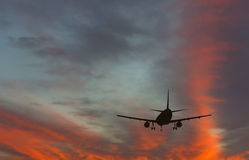 Silhouette Of Landing Airplane At Dawn Stock Photos