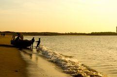 Free Silhouette Of Men Pushing A Tourist Fishing Boat Into The Ocean At A Gujarat Beach Stock Photography - 142833902