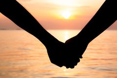 Free Silhouette Of Romantic Couple Holding Hands And Watching A Beautiful Sunset On The Seashore. Love And Valentine Concept Royalty Free Stock Photo - 165901815