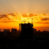 Silhouette Of The Tower Crane On The Construction Site With City Building Stock Photo