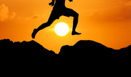 Silhouette Of Theyoung Man Jumpping At Mountain Yellow Sunset Ba Royalty Free Stock Photo
