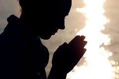 Silhouette Of Woman Prays Stock Photography