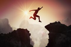 Free Silhouette Of Young Man Jumping Over Mountains And Cliffs At Sunset Stock Photos - 109182693