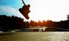 Free Silhouette Of Young Skater Jumping On Ramp At City Park - Boy Performing Tricks And Skills With Skateboard At Sunset  - Youth Royalty Free Stock Images - 169960299
