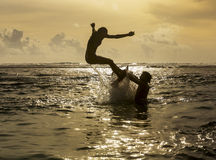 Silhouette Of Young Woman Jumping Out Of Ocean Stock Photography