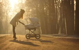 Free Silhouette Of Young Woman On Sunny Footpath And Looking At Child In Baby Stroller. Sunny Winter Park, Childcare And Love Royalty Free Stock Photos - 172376858