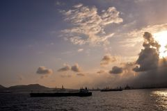 Silhouette of an offshore drilling rig. And supply vessel at sunset Stock Photo