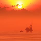 Silhouette Offshore Jack Up Drilling Rig and Boat Royalty Free Stock Images