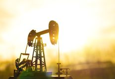 Silhouette of an oil drilling pump against a background. Of sun rays in the sunset stock photography