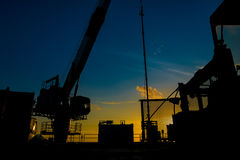 Silhouette of oil and gas wellhead platform and well service worker while working to perforation gas and crude oil reservoir. Silhouette of oil and gas wellhead Royalty Free Stock Images