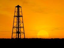 Silhouette oil pump. Oil pump silhouette over orange sky Stock Images