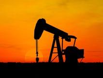 Silhouette oil pump. Oil pump silhouette over orange sky Stock Photo