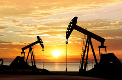 Silhouette of oil pumps. Silhouette of working oil pumps on sunset background Royalty Free Stock Images