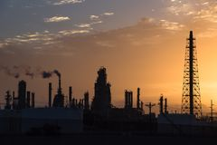 Oil refinery silhouette at sunrise. Silhouette oil refinery at sunrise. Oil factory, petrochemical plant tower, gas flare, smoke stacks and machinery in Corpus Royalty Free Stock Photos