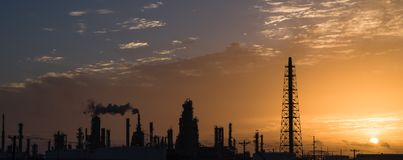 Oil refinery silhouette at sunrise. Silhouette oil refinery at sunrise. Oil factory, petrochemical plant tower, gas flare, smoke stacks and machinery in Corpus Royalty Free Stock Image
