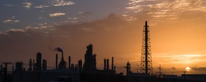 Oil refinery silhouette at sunrise. Silhouette oil refinery at sunrise. Oil factory, petrochemical plant tower, gas flare, smoke stacks and machinery in Corpus Royalty Free Stock Photo