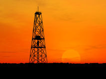Silhouette oil rig. Oil rig silhouette over orange sky Royalty Free Stock Photography