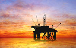 Silhouette oil rig. Oil rig silhouette over orange sky Stock Image