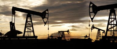 Silhouette of oil rig at sunset the sun. Silhouette of an oil rig at sunset the sun royalty free stock photography