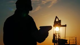 Silhouette of oilfield worker at crude oil pump in the oilfield at golden sunset. Industry, oilfield, people and. Development concept stock video