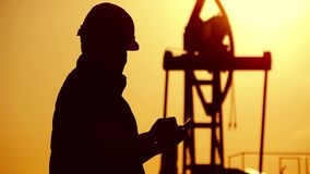 Silhouette of oilfield worker at crude oil pump in the oilfield at golden sunset. Industry, oilfield, people and. Development concept stock footage