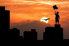 Silhouette of old  building and boy. Silhouette of high old building and boy hold bubble and sunset background Stock Photo