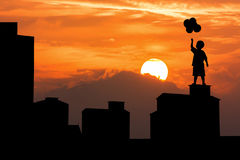 Silhouette of old  building and boy. Silhouette of high old building and boy hold bubble and sunset background Royalty Free Stock Image