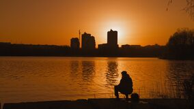 Silhouette Fisherman with fishing rod on the riverbank in the Light of the Orange Sunset