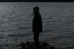 Silhouette of an old fisherman smoking a pipe. Side view silhouette portrait of an old fisherman standing at the edge of the water smoking a pipe, with his hands Royalty Free Stock Image
