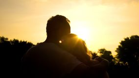 Silhouette of old hugging couple, watching sunset together, secure old age royalty free stock photography