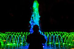 Silhouette of an old man in front of fountain with colored illumination royalty free stock images